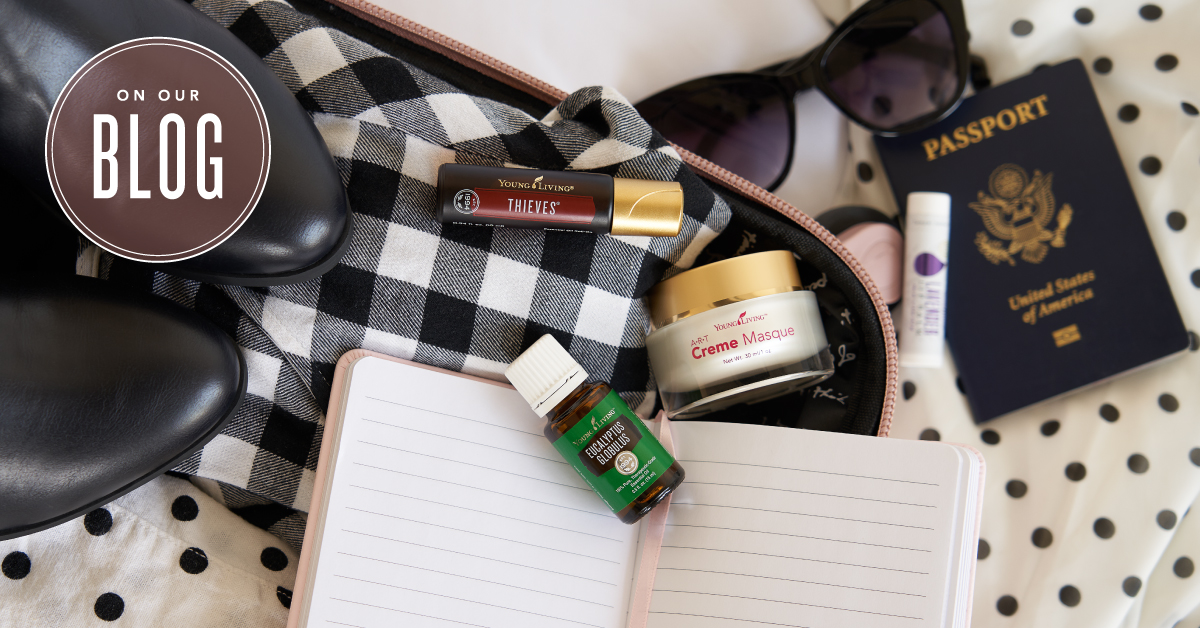 An open suitcase packed with clothes and essential oils for travel: Breathe again roll on, eucalyptus globulus essential oil, and ART creme masque